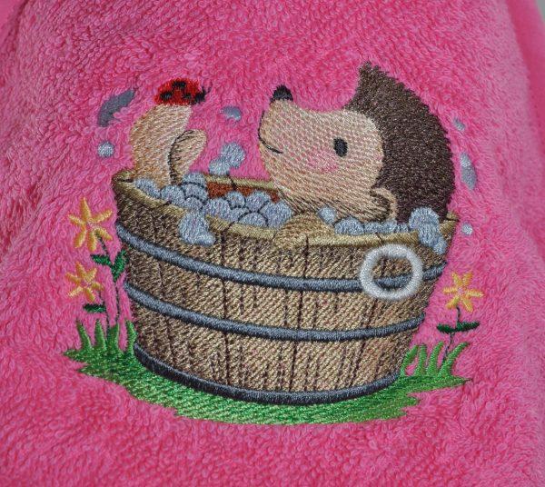 Cape de bain personnalisée brodée d'un hérisson dans sa baignoire