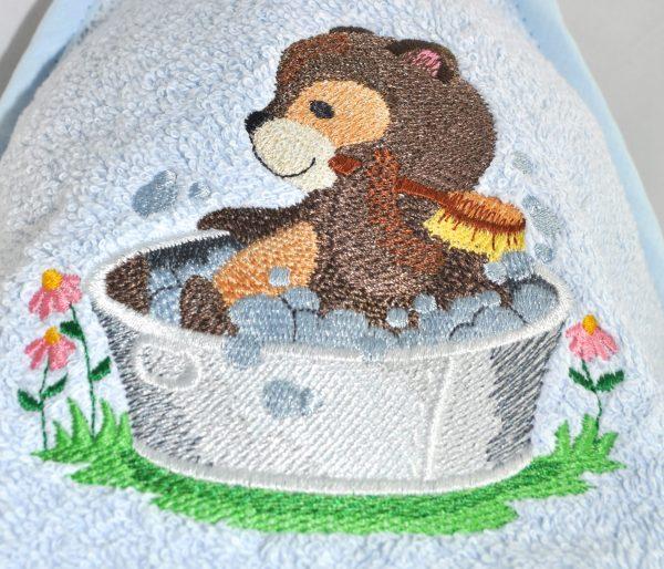 Cape de bain personnalisée brodée d'un ourson dans sa baignoire